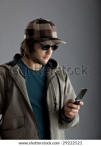 Good looking young man wearing a sunglasses and using a cellphone - stock photo