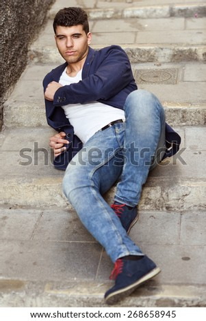 Good looking young man with blue eyes in the street. Model of fashion sitting in urban stairs wearing white t-shirt, jeans and blue jacket - stock photo