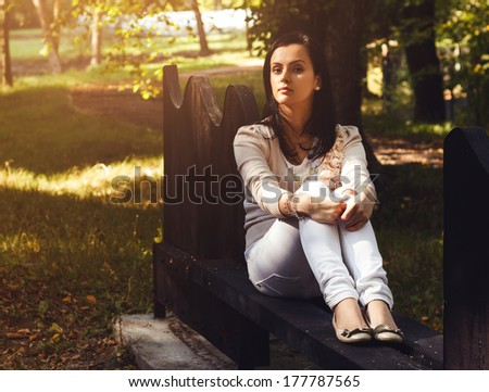 Good looking young woman sitting on a bench in the park and looking to camera - stock photo