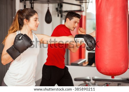 Good looking young woman with boxing gloves practicing on a punching bag next to her instructor - stock photo