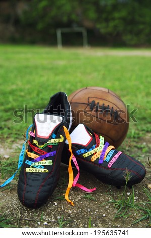 Good luck soccer football boots soccer cleats laced with Brazilian wish ribbons on rustic dirt grass pitch with vintage brown football