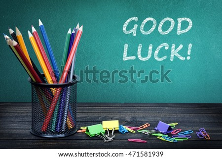 Good luck text on green board and group of pencils
