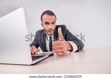 Good luck to you. Smiling African businessman sitting at a desk on a laptop while businessman sitting at the table and showing thumb up over a laptop isolated on a gray background