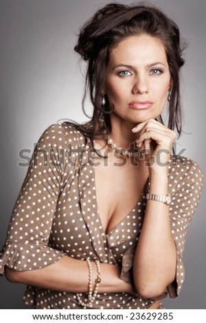 Good lucking adult woman wearing necklace of pearl looks at the camera. Focus on the eyes and hands. - stock photo