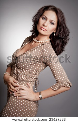 Good lucking attractive woman posing in a dress. Retro celebrity style portrait. - stock photo