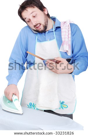Good man is ironing, cooking and speaking on phone - stock photo