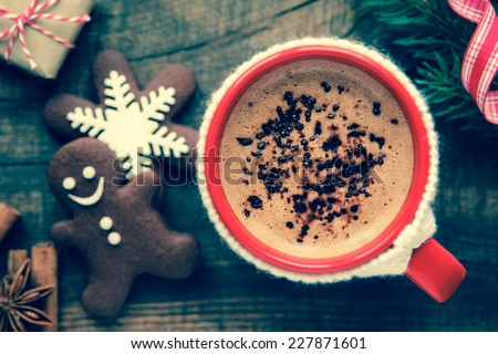 Good morning Christmas concept - red cup of coffee with decorated xmas snowflake and gingerbread cookies surrounded with festive decoration and gifts. With retro vintage filter effect - stock photo