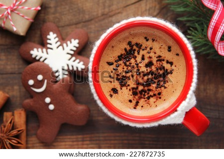 Good morning Christmas concept - red cup of coffee with decorated xmas snowflake and gingerbread cookies surrounded with festive decoration and gifts - stock photo