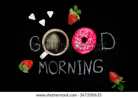 Good morning greeting written on black chalk board. Donut (doughnut), cup of black coffee, strawberries and heart shaped sugar cubes. Happy Valentines Day Food - stock photo