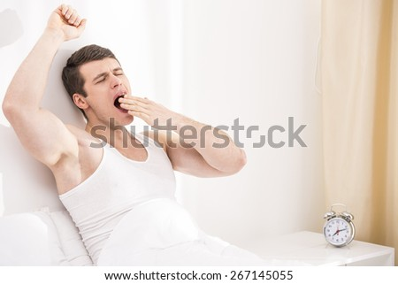 Good morning. Handsome young male waking up on bed. - stock photo