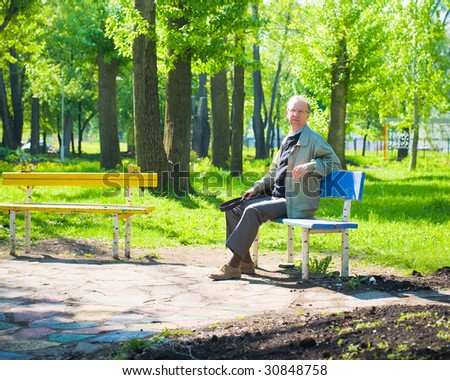 Good morning  in park. Mature man sits on a bench - stock photo