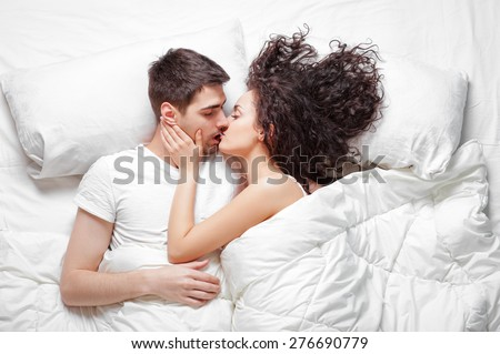 Good morning! Love and comfort. Overhead of happy beautiful young couple lying on the bed kissing and hugging. Top view. - stock photo