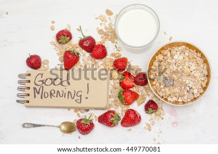 Good morning note in a notebook with craft brown pages, ripe strawberries, milk and oat muesli for breakfast - stock photo