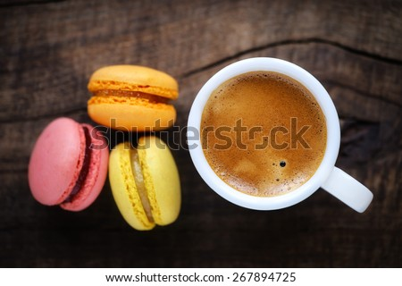 Good morning or Have a nice day message concept - white cup of frothy espresso coffee with colourful French macarons on dark rustic wooden background - stock photo