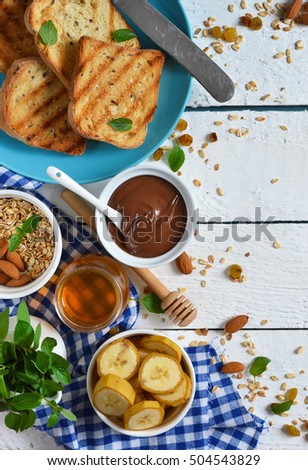 Good morning - toast with chocolate paste, banana and honey. White food background.