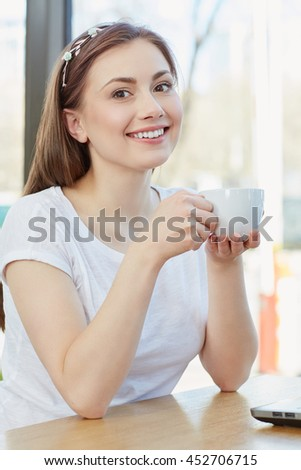 Good morning. Vertical portrait of a beautiful cheerful female enjoying her cup of coffee at the cafe smiling to the camera - stock photo