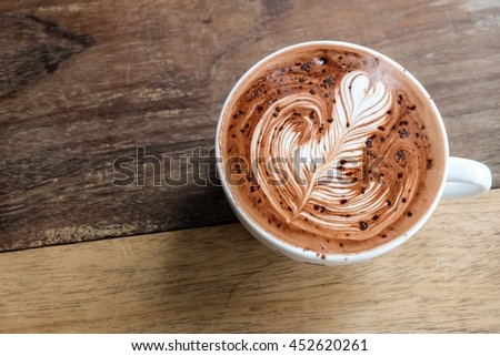 Good morning with hot chocolate on wood table, beautiful art on cup of hot chocolate  - stock photo