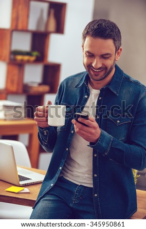 Good news from colleague. Handsome young man holding coffee cup and looking at his smart phone with smile while standing near his working place in office - stock photo