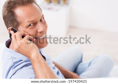 Good news from friends. Top view of cheerful mature man talking on the mobile phone and looking over shoulder while sitting on the couch at home - stock photo