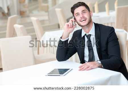Good news on the phone. Young and motivated businessman is sitting at the table with tablet and mobile phone. Man is in a good mood and smiling, while doing his job