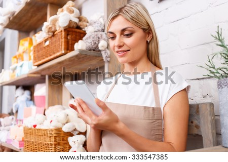 Good news. Pleasant charming professional florist holding mobile phone and keeping glance down while resting  - stock photo