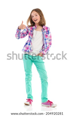 Good news. Young girl in lumberjack shirt and green trousers showing thumb up. Full length studio shot isolated on white. - stock photo