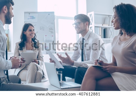 Good news! Young handsome man discussing something with his coworkers with smile while sitting on the couch at office  - stock photo