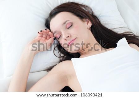 Good night: portrait of a beautiful caucasian woman sleeping on a pillow - stock photo