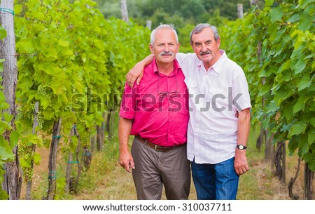 Good old friends and agrarians posing to camera on their beautiful grape fields. - stock photo