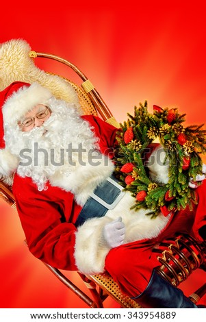 Good old Santa Claus sitting in a rocking chair and holding Christmas wreath. Red background. Christmas. - stock photo