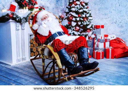 Good old Santa Claus sitting in a rocking chair in the room by the fireplace and Christmas tree, beautifully decorated for Christmas. - stock photo