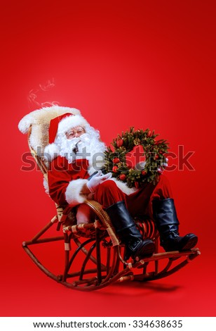 Good old Santa Claus sitting in a rocking chair over red background. Christmas. - stock photo