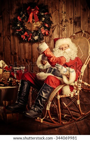Good old Santa Claus with Christmas gifts at his wooden house. Sepia.  - stock photo