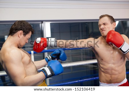 Good punch. Boxer punching his opponent on the ring - stock photo