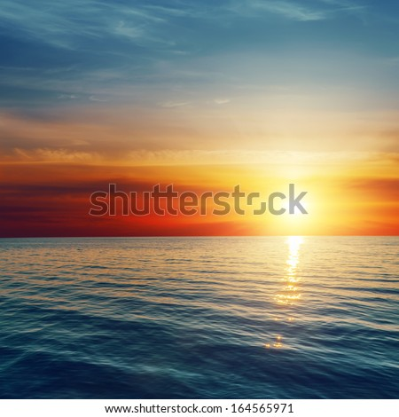 good red sunset over darken sea - stock photo