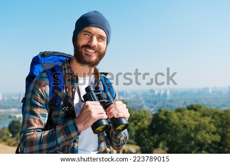 Good scenery. Handsome young man carrying backpack and looking at camera with smile while standing in the nature and holding binoculars - stock photo