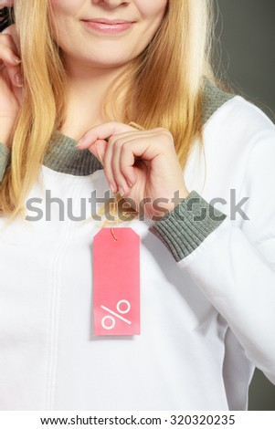 Good shopping sale concept. Blonde fashionable woman holding discount red label with percent sign in hand, closeup - stock photo