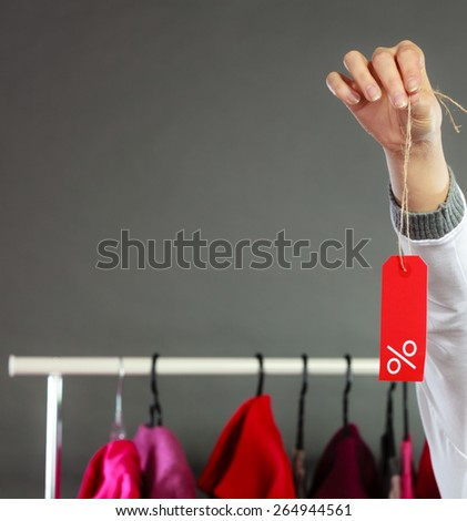 Good shopping sale concept. woman choosing clothes holding discount red label with percent sign in hand - stock photo