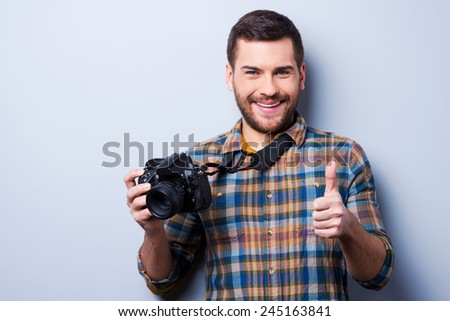 Good smile!. Portrait of confident young man in shirt holding camera and showing thumb up while standing against grey background - stock photo