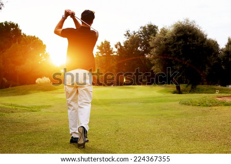 Good strike, golfer swinging his driver and looking away while standing on golf course, professional golfer looking trajectory of the ball, golfer hitting golf ball standing on course at sunny evening - stock photo