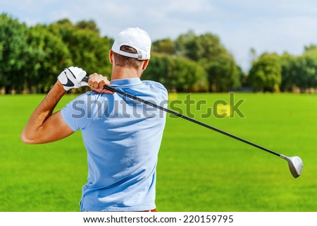Good strike. Rear view of male golfer playing golf while standing on green - stock photo