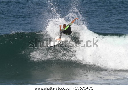 good surfer in action on a wave - stock photo