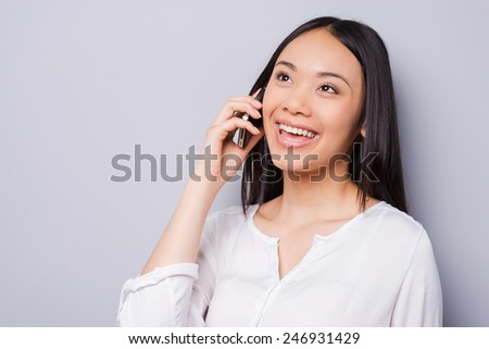 Good talk. Beautiful young Asian woman talking on the mobile phone and smiling while standing against grey background - stock photo