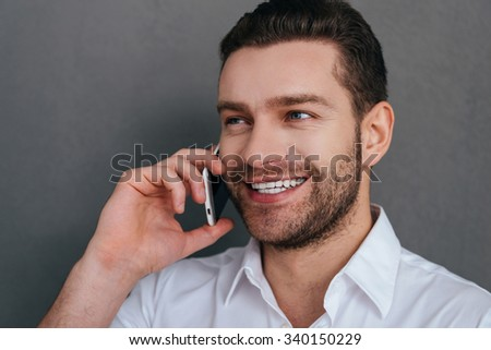 Good talk. Handsome young man talking on the mobile phone and smiling while standing against grey background  - stock photo