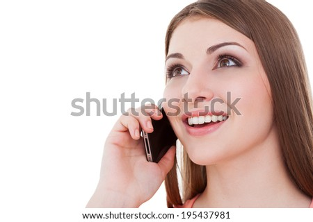 Good talk. Happy young woman talking on the mobile phone and smiling while standing isolated on white