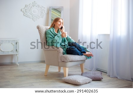 Good talk.Technology and coziness. Beautiful young woman with cup of tea talking by smart phone while sitting on armchair at home. - stock photo