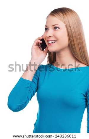 Good talk with friend. Beautiful young women talking on the mobile phone and smiling while standing against white background