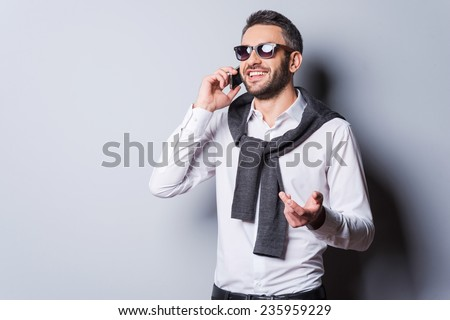 Good talk with friend. Handsome young man in smart casual wear and sunglasses talking on the mobile phone and smiling while standing against grey background - stock photo
