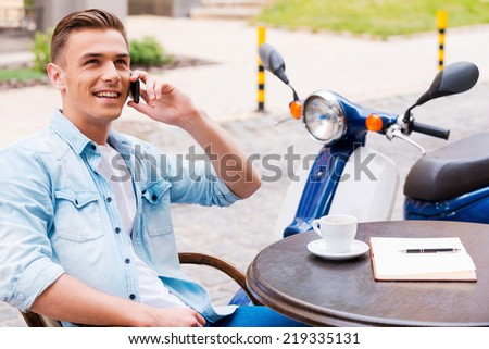 Good talk with friend. Relaxed young man talking on the mobile phone and smiling while sitting in sidewalk cafe  - stock photo