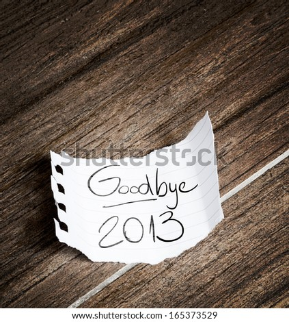 Goodbye 2013 written on the paper on a wood background - stock photo